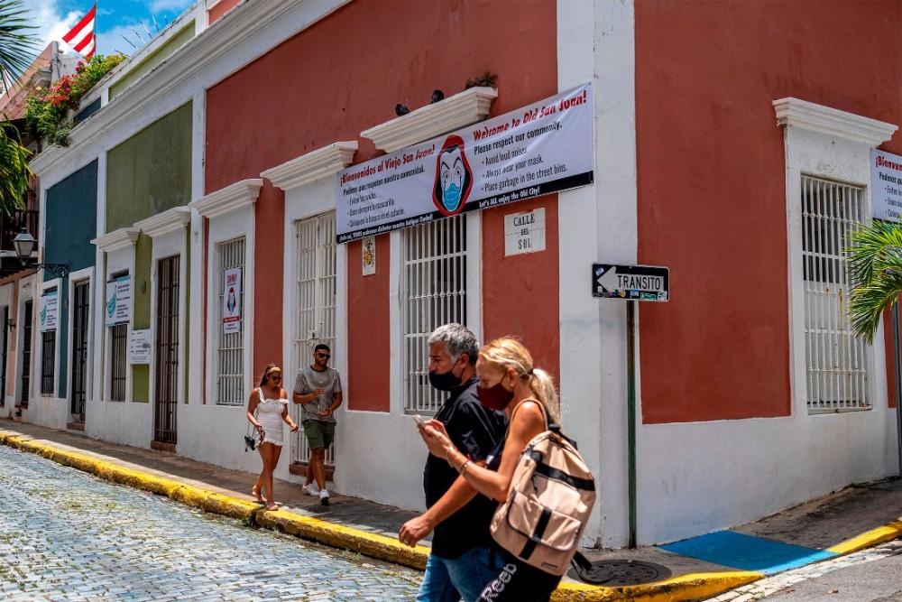 pareja camina con mascarillas por San Juan, Puerto Rico