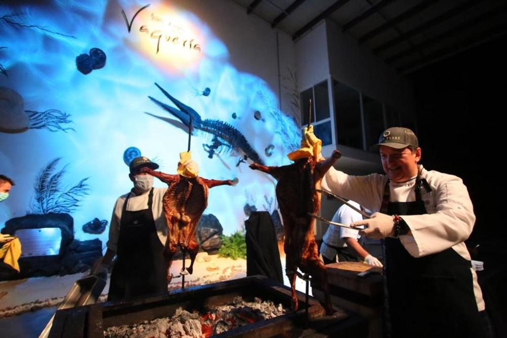 El chef Juan Ramón Cárdenas presentando un cabrito al pastor en Bodega San Juan de la Vaquería con su ícono paleontológico de fondo